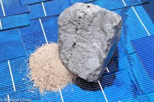 Bergje zand en blokje silicium op een ondergrond van zonnecellen