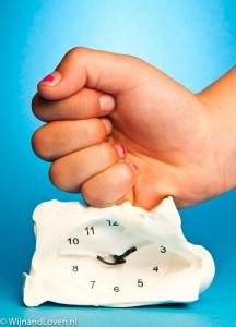 Foto concept van De tijd doden - een kinderhand 'slaat' een klok plat.