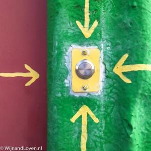Foto een gele deurbel op een groene achtergrond (en vier pijlen).