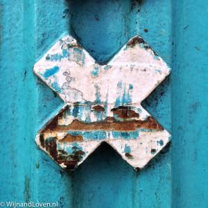 Foto van een kruis op een turquoise achtergrond.
