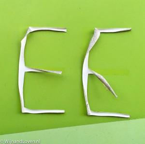 Foto in de categorie cijfers en letters: twee stickers van de letter E die los hebben gelaten van de groene ondergrond.