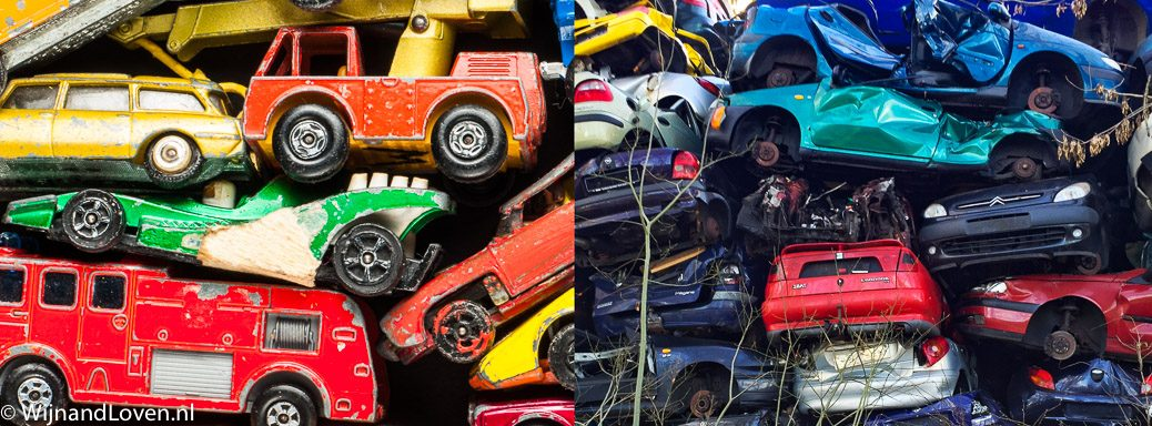 Studio-foto van een stapel speelgoed-autootjes en een stapel auto's in een sloperij